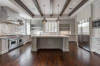 White and gray kitchen features a tray ceiling lined with ...