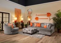 The application of orange and cool grey in this living ...