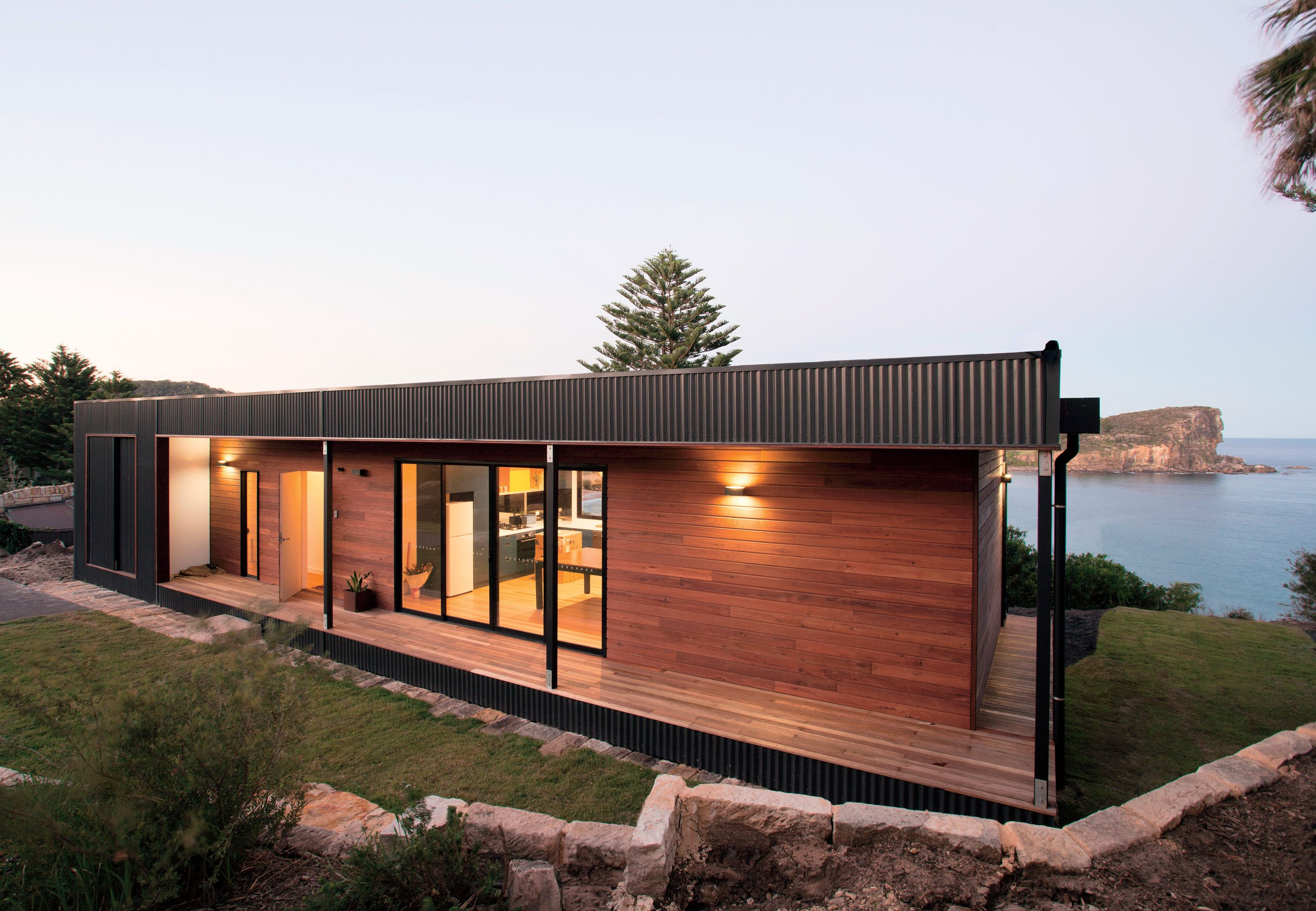 Exterior materials modern beachside prefab home in australia by archiblox with colorbond ultra steel and queensland blue gum wood claddingon the facade