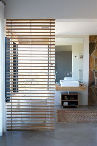 The slatted wooden room divider in the bathroom in the ...