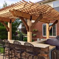 This image features a pergola, built over a patio grill ...