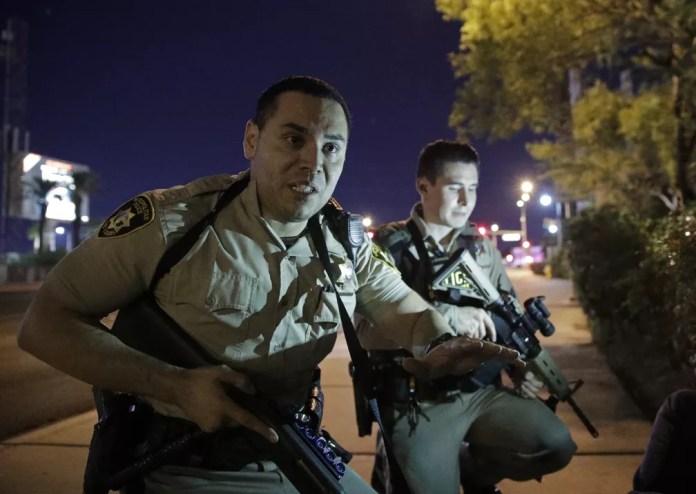 Policiais pedem para pessoas se protegerem perto de local em que tiros foram ouvidos em Las Vegas (Foto: John Locher/AP)