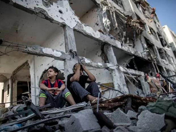 Irmãos palestinos sentados diante do prédio onde moravam na cidade de Beit Hanun, destruída durante conflito entre Israel e Hamas na Faixa de Gaza (Foto: AFP Photo/Marco Longari)