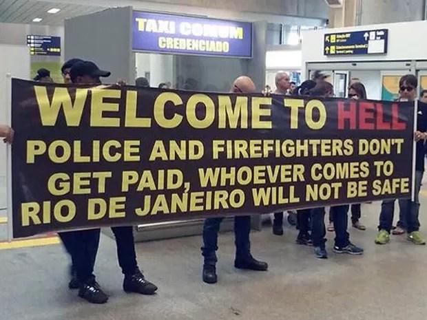 Policiais levaram faixa para o galeão com os dizeres, em inglês: 'Bem-vindo ao inferno' (Foto: Reprodução/Globo)