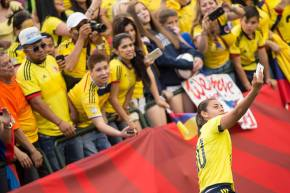 A Columbian player snaps a photo with the crowd.