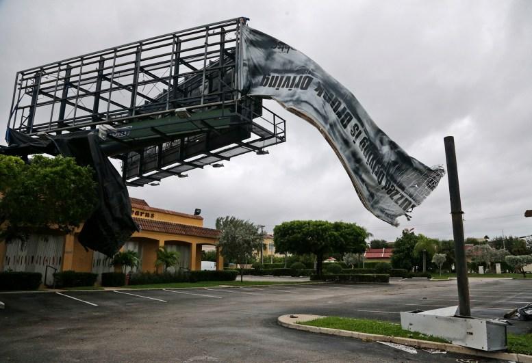 Un letrero roto ondea en el viento en North Palm Beach (AP Photo/Wilfredo Lee)