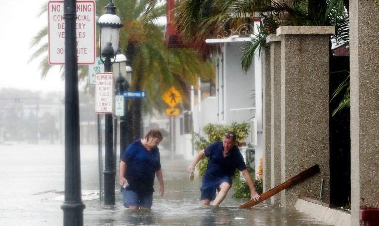 Un hombre y una mujer tratan de abrirse paso en una calle inundada en St. Augustine (AP Photo/John Bazemore)