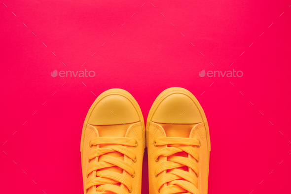 Yellow canvas shoes sneakers on neon pink background Stock Photo by