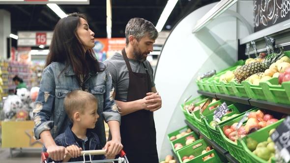 Sociable Handsome Shop Assistant Is Selling Fresh Fruit To - shop assistan