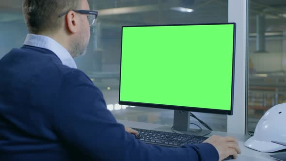 Chief Engineer Works on His Computer with Mock-up Green Screen by