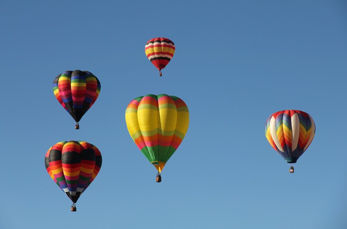 Colorful Hot Air Balloons Floating Against a Blue Sky Wall Mural