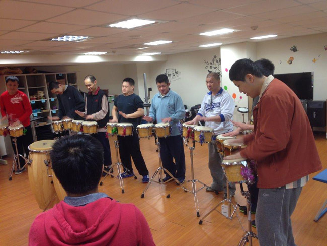 Volunteers and disadvantaged residents playing drums