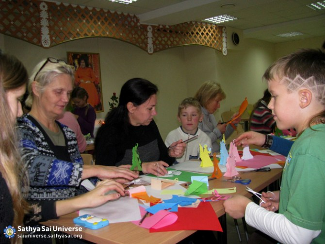 Adults helping Children make Paper Angels