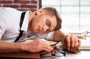 Sleeping author. Handsome young man in shirt and tie sleeping while sitting at the desk