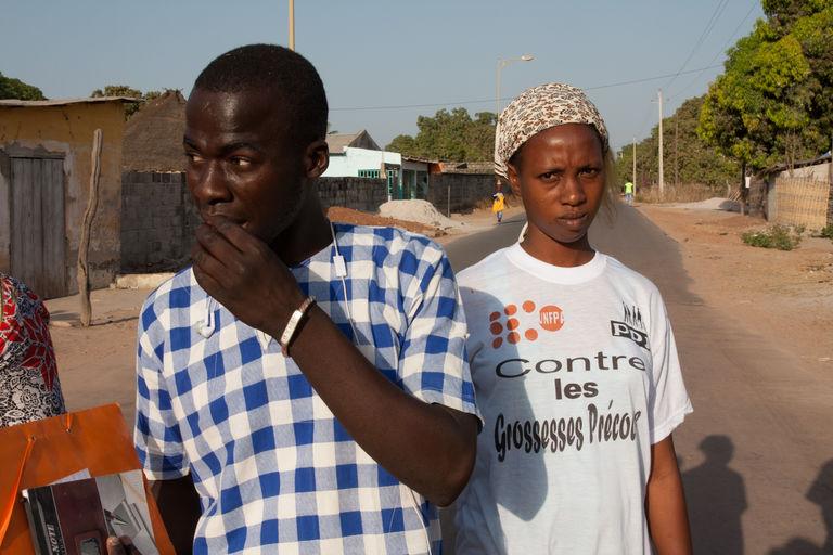 Un pair éducateur et une membre du club de jeunes filles de Sintian sillonnent le quartier pour recenser les enfants fantômes.