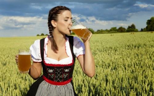 Bavarian girl in Dirndl drinking two beer steins