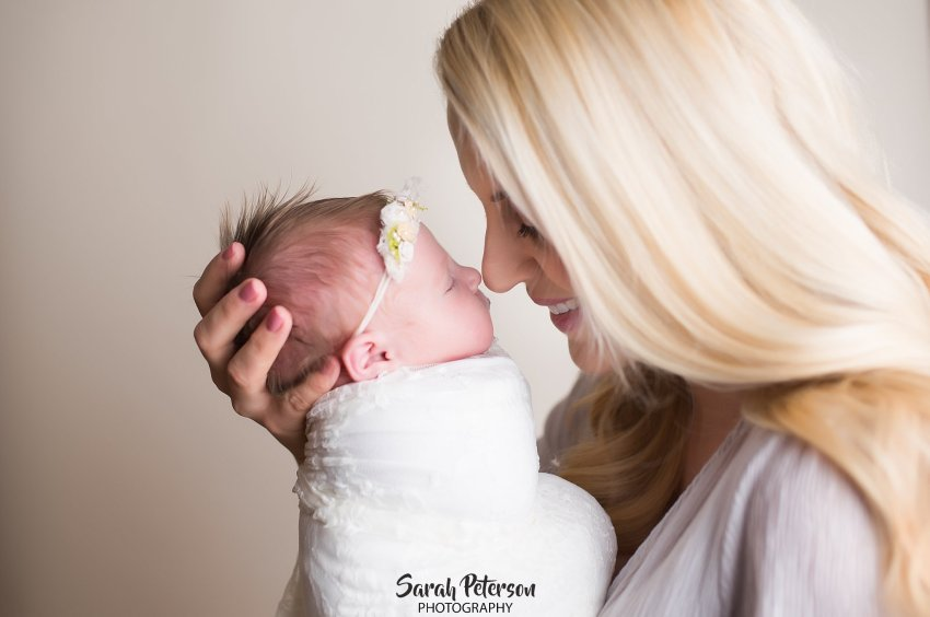 Mom holding newborn baby girl nose to nose