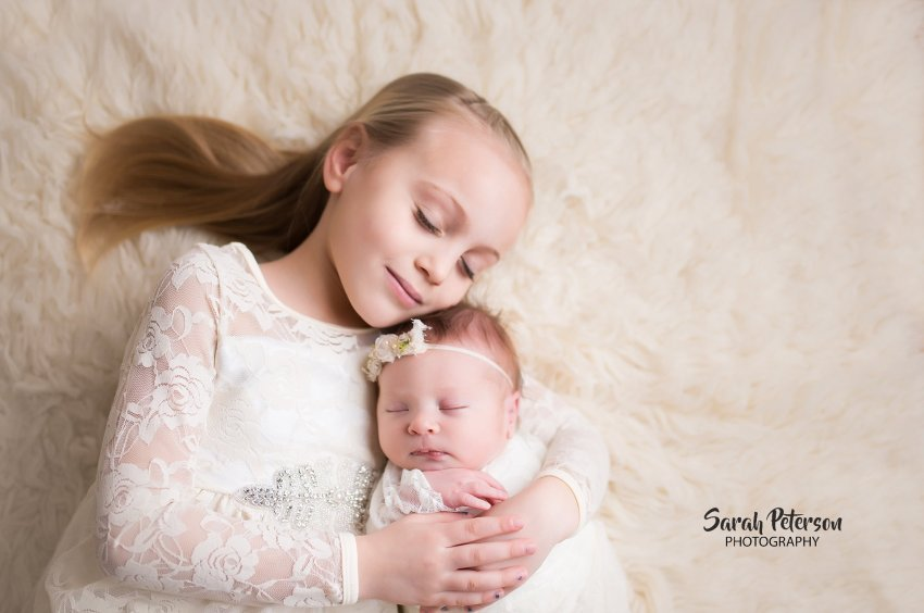 big sister holding newborn baby girl with eyes closed