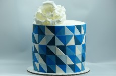 Tall cake with blue triangles with giant rose