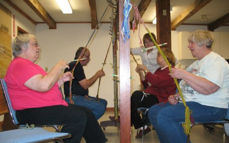 Fingerweaving Class, Fall 2008, Students use leg elastic to control tension