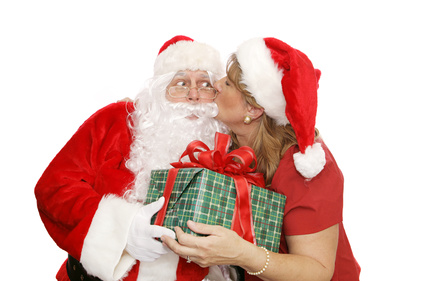 Mrs Santa giving Santa a thank you kiss as he hands her a Christmas present.  Isolated on white.