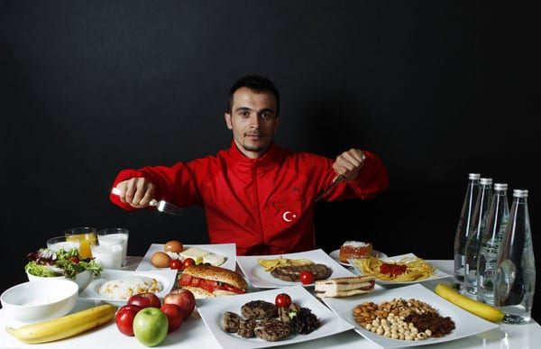 Turkish weightlifter and Olympic hopeful Mete Binay, 27, poses in front of his daily meal intake in Ankara May 29, 2012. Binay is a world champion weightlifter and his daily diet is 3500 kcal. He drinks at last two glasses of milk every night. His diet is largely composed of red meat. He consumes plenty of sweet desserts everyday and takes care never to miss a full breakfast. Binay is also keen on organic food. Shortly before competitions he begins to supplement his diet with ergogenic aids and vitamin pills. Picture taken May 29, 2012. REUTERS/Umit Bektas (TURKEY - Tags: FOOD HEALTH SPORT OLYMPICS WEIGHTLIFTING PORTRAIT)   ATTENTION EDITORS: PICTURE 17 OF 24 FOR PACKAGE 'AN OLYMPIAN DIET'  SEARCH 'UMIT DIET' FOR ALL IMAGES