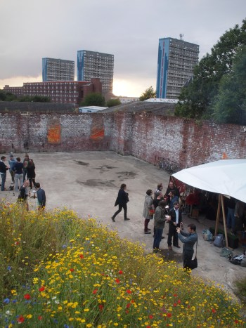 A group of young people discussing plans in a walled space, behind the skyline is dominated by high rise flats