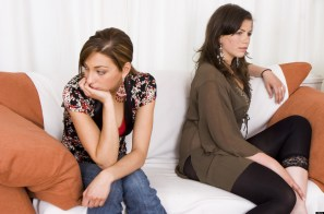 BWNT23 Two upset teenage girls sitting on sofa indoors at home