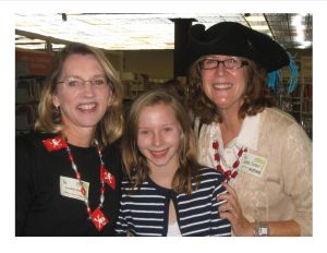 Carolyn Henger Oaks (left) currently manages the author visit grant requests from schools. She's pictured with her daughter, Maggie, and author June Sobel during a pirate-themed Family Night event.