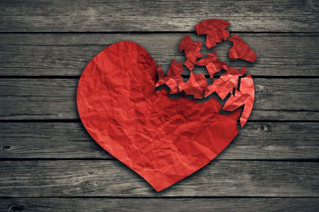 40353077 - broken heart breakup concept separation and divorce icon. red crumpled paper shaped as a torn love on old wood symbol of medical cardiovascular health care problems due to illness