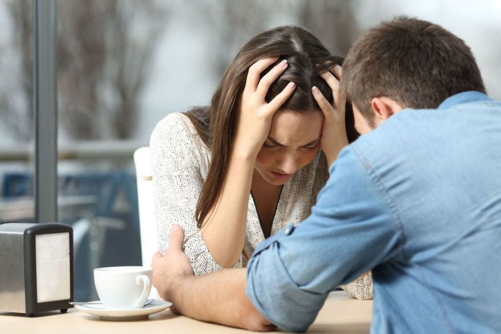 56102113 - male comforting to a sad depressed female who needs help in a coffee shop. break up or best friend concept