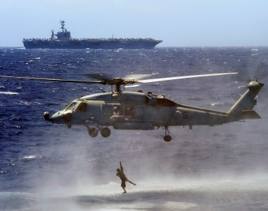 Explosive Ordnance Disposal Technician 2nd Class Nathan Albrich climbs a ladder to an HH-60H Sea Hawk during training July 20 in the western Pacific, with George Washington in the background.//Navy/MC3 Adam K. Thomas