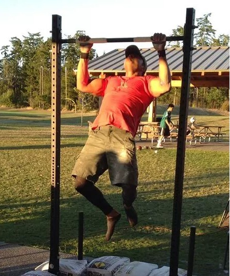 AC2 McCastle performs pullups July 26 at Fort Nugent Park in Oak Harbor, Washington. He came within 900 reps of the world record. (Photo courtesy AC2 McCastle)