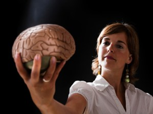Young woman holds an accurate medical model of a human brain. Camera: Canon EOS 1Ds Mark III.
