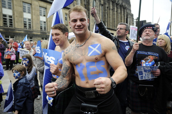 """A pro-independence supporter with a Saltire flag and a """"Yes"""" written on his body joins a march and rally in Edinburgh on September 21, 2013 in support of a yes vote in the Scottish Referendum to be held in September 2014. Voting for Scottish independence is """"common sense"""", First Minister Alex Salmond, the leader of the movement to break away from the United Kingdom insisted on September 18 a year to the day before Scotland votes in a referendum. AFP PHOTO / ANDY BUCHANAN        (Photo credit should read Andy Buchanan/AFP/Getty Images)"""