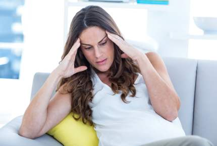 Depressed pregnant woman with hands on head sitting on sofa