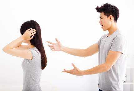 Angry young couple arguing in living room