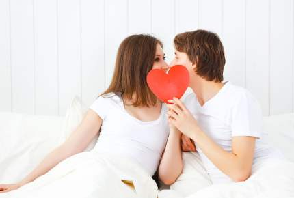 lover couple kissing with a red heart in bed