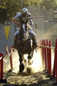 man on a horse jousting red fence on the side yellow and green flag in background
