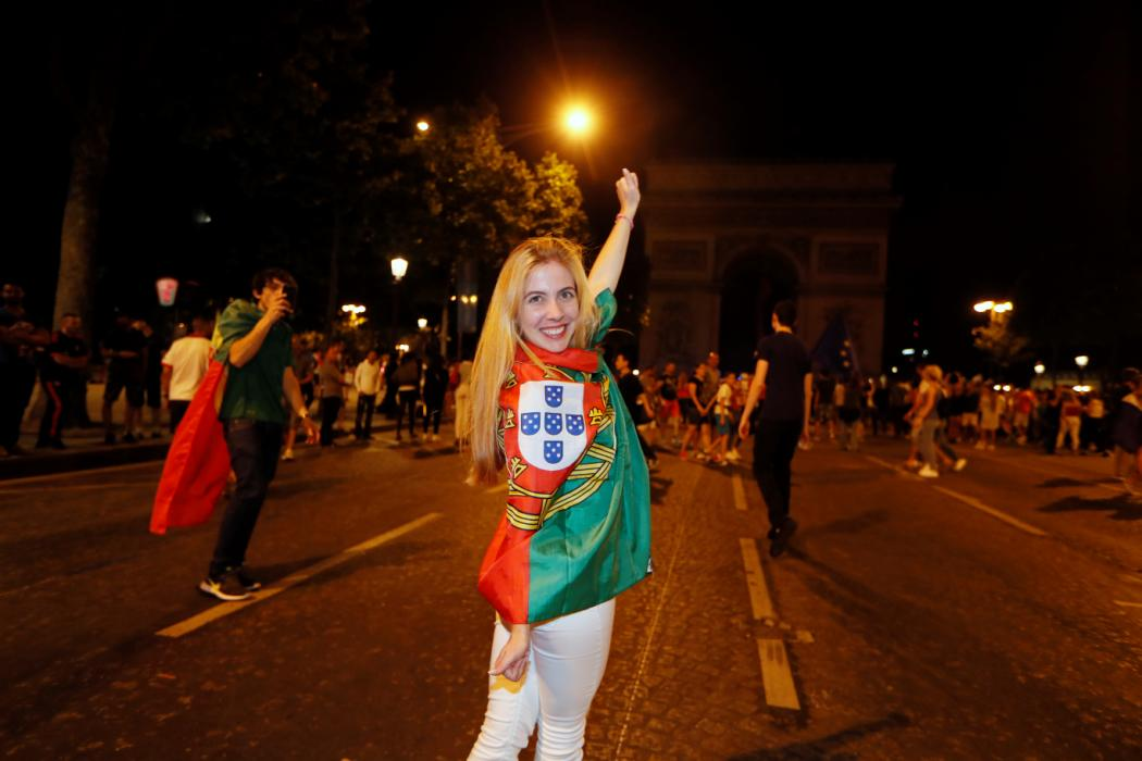 A Portugal supporter celebrates victory near the Arc de Triomphe after the Euro 2016 football tournament final match between Portugal and France on July 10, 2016 in Paris. / AFP PHOTO / Thomas SAMSON