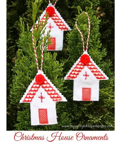Tres casitas de fieltro en blanco y rojo colgadas de unos árbolitos