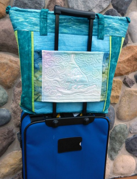 """I also used the batik technique to put our logo on the pocket on the back of the bag. Kathy's pattern is meant for a travel bag and this pocket has Velcro at the bottom, so the bag can be placed over the handle of a wheeled suitcase!"""