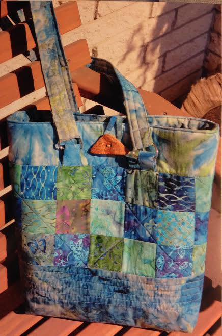 "by Pam Merklein - ""I used the fabric you gave us for the top portion of my ""Oak Park Bag"" and for the tabs and loop. The button was purchased in Tallinn, Estonia. I had a charm pack at home that provided the squares and the balance of the fabric was left from a senior HS gift quilt for my grandson. I look forward to using it and being reminded of our wonderful trip."""