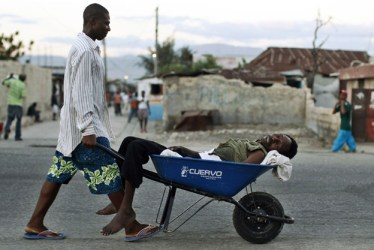 Man carries cholera victim in wheelbarrow Cite Soleil Port au Prince Haiti 2010 by Eduardo Munoz, Reuters