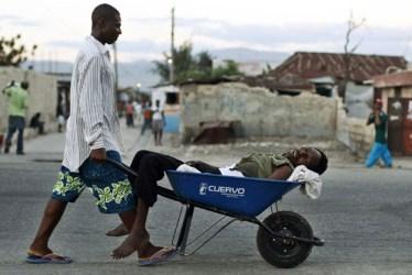 Man carries cholera victim in wheelbarrow Cite Soleil Port au Prince Haiti 2010 by Eduardo Munoz, Reuters
