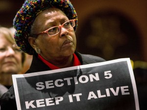 Woman holds sign 'Section 5 Keep it alive' as Supreme Court hears Voting Rights Act challenge 022713
