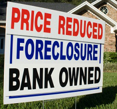 'Price Reduced, Foreclosure, Bank Owned' sign on lawn