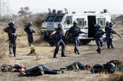 A policeman gestures in front of some of the dead miners after they were shot outside a South African mine in Rustenburg