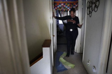 Another Treasure Island resident, Sandy Agee, shows a Chronicle reporter the problems that arose after her bathroom flooded. – Photo: Lea Suzuki, San Francisco Chronicle