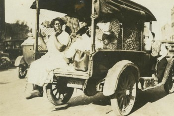 Women taken prisoner ride in a paddy wagon, an armed white guard – probably a police officer – riding on the running board. – Photo: Tulsa Historical Society